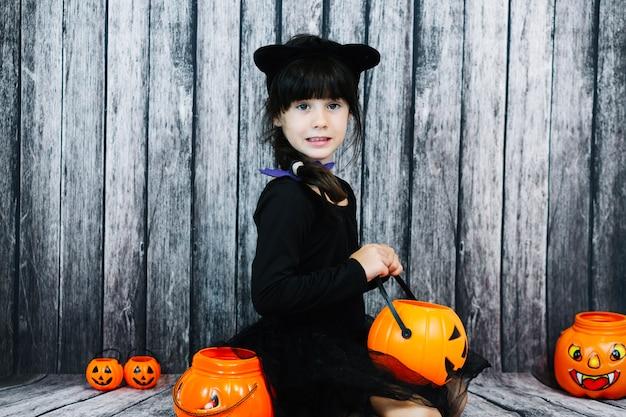 Girl in cat costume holding jack-o-lantern basket