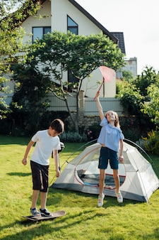Girl catching butterflies with scoop net and boy playing skateboard near tent camp