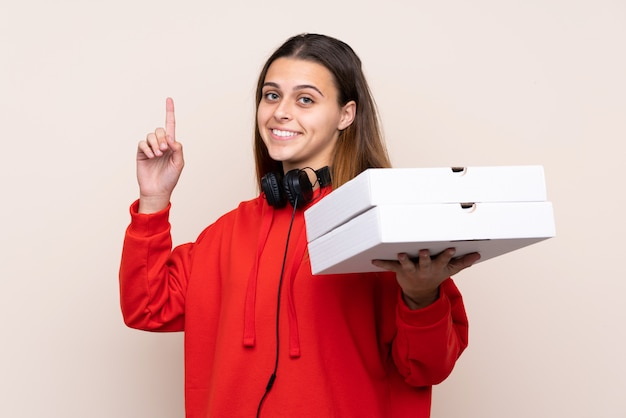 Girl catching pizza boxes over isolated wall