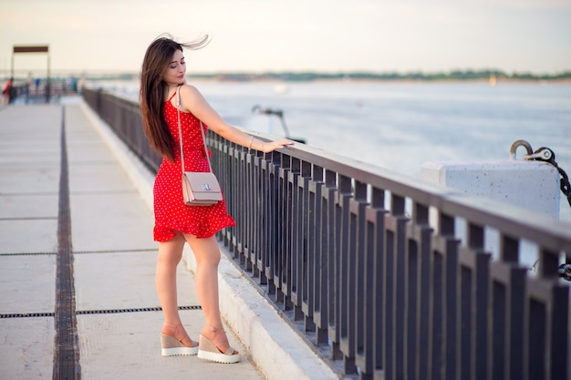 A girl of caucasian ethnicity with long hair in a red summer dress walks along the embankment of the river