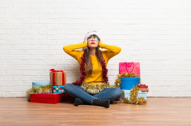 Girl celebrating the christmas holidays covering both ears with hands