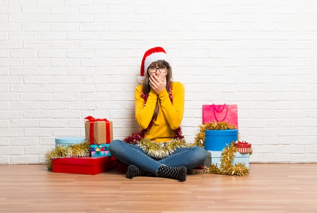 Girl celebrating the christmas holidays covering mouth with hands