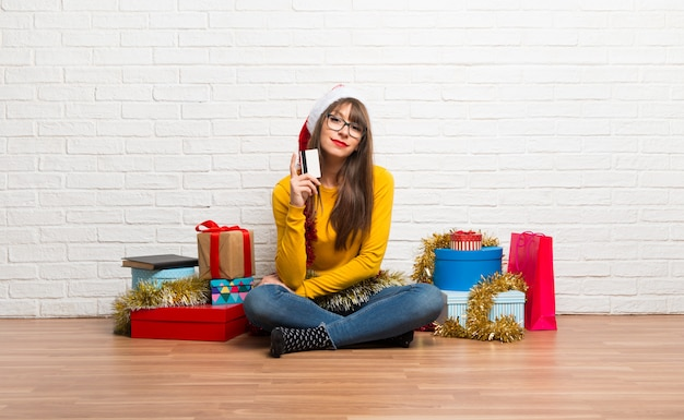 Girl celebrating the christmas holidays holding a credit card