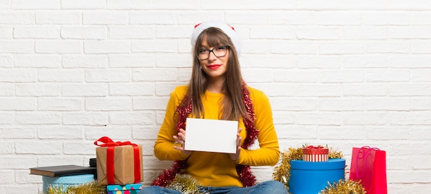Girl celebrating the christmas holidays holding an empty white placard for insert a concept
