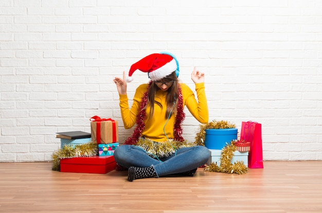 Girl celebrating the christmas holidays listening to music with headphones and dancing