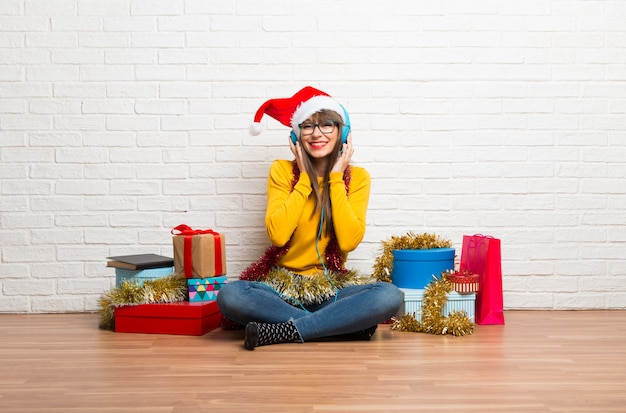 Girl celebrating the christmas holidays listening to music with headphones