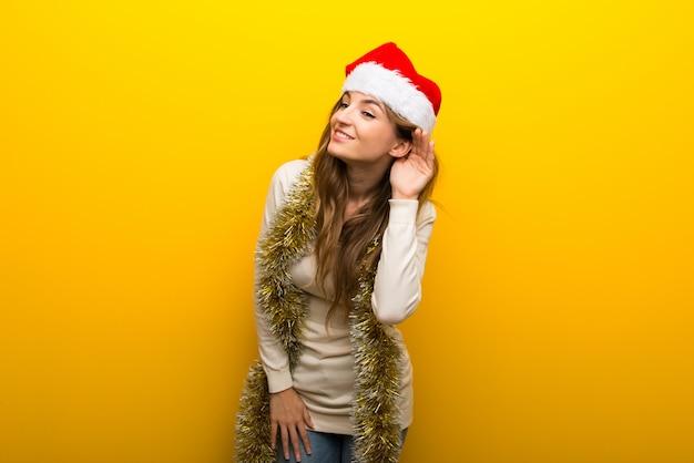 Girl celebrating the christmas holidays on yellow background