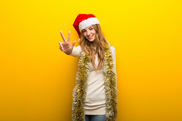 Girl celebrating the christmas holidays on yellow background