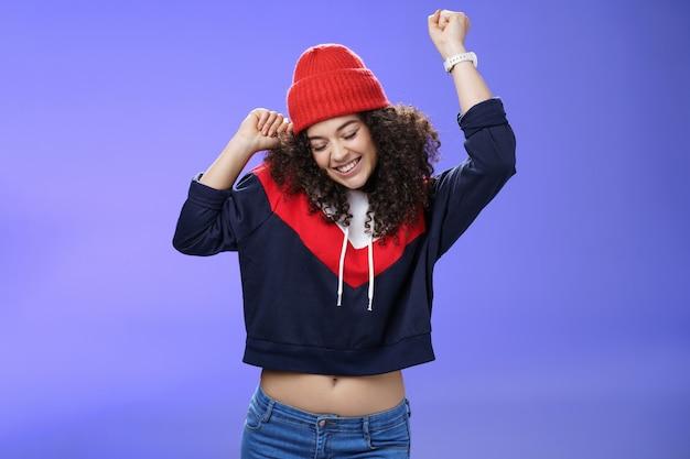 今年の好きな季節を祝う女の子。音楽と休日を楽しんで笑っているダンスの動きで手を持ち上げるかわいい赤い帽子の巻き毛を持つのんきで楽しい踊る女性の肖像画。