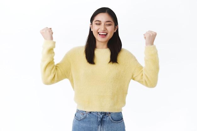 축하하는 소녀는 좋은 소식을 듣고, 만세 제스처로 손을 들고, 주먹 펌프 테스트를 성공적으로 마치고, 낙관적으로 웃고, 행운과 기쁨을 느끼고, 챔피언이 되고, 흰 벽