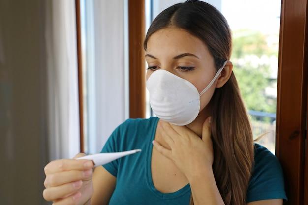 女の子はコロナウイルス病2019の症状の1つである発熱をチェックします。
