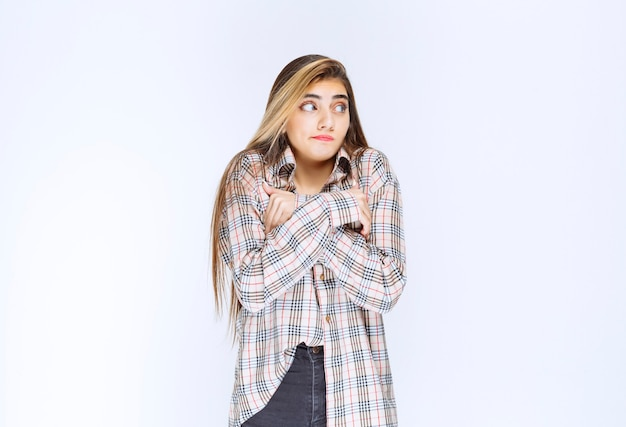 Girl in checked shirt crossing arms and feeling cold