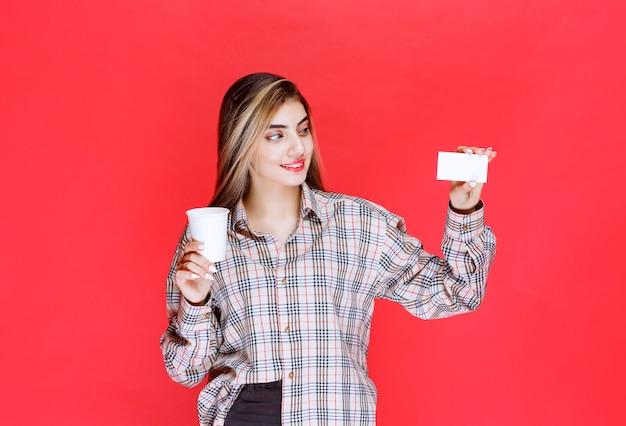 Ragazza in camicia a quadri che tiene una tazza di caffè e presenta il suo biglietto da visita