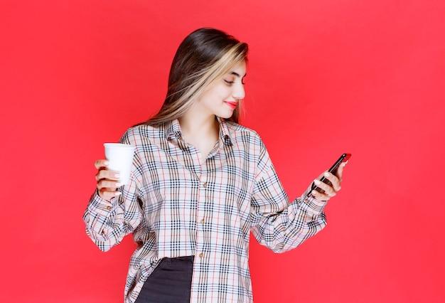 Ragazza in camicia a quadri che tiene una tazza di bevanda e gioca con il suo smartphone