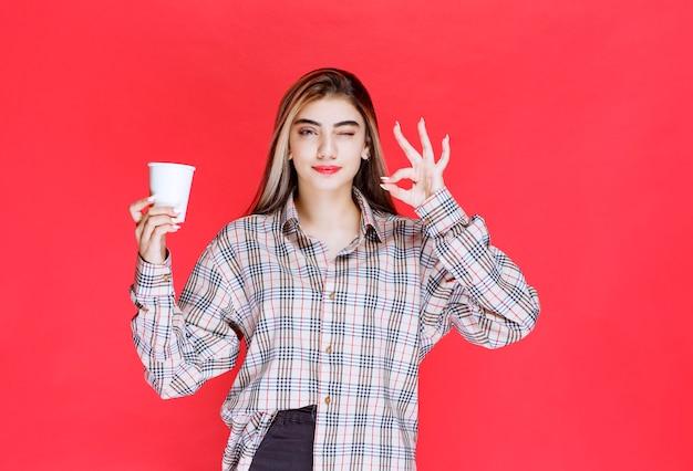 Ragazza in camicia a quadri che tiene in mano una tazza di caffè usa e getta bianca e si gode il gusto