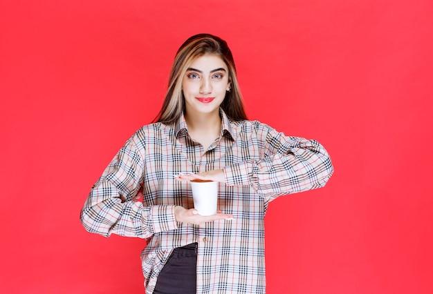 Ragazza in camicia a quadri con in mano una tazza di caffè usa e getta bianca