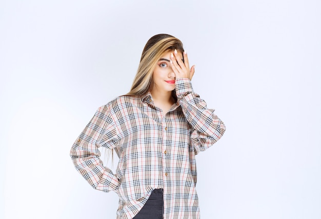 Girl in checked shirt looking across her fingers