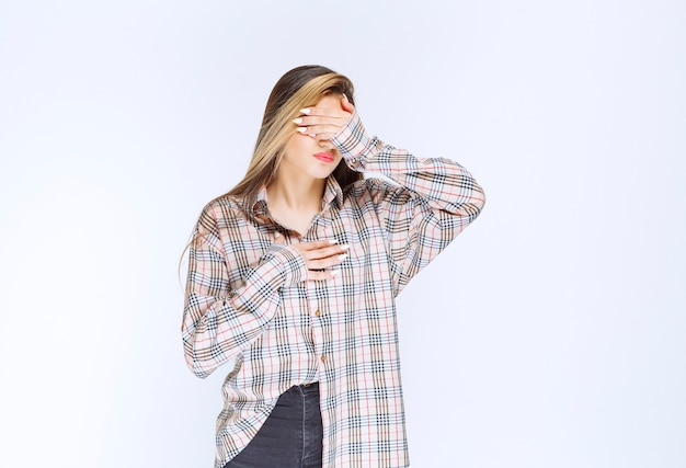 Girl in checked shirt looks pale and sleepy