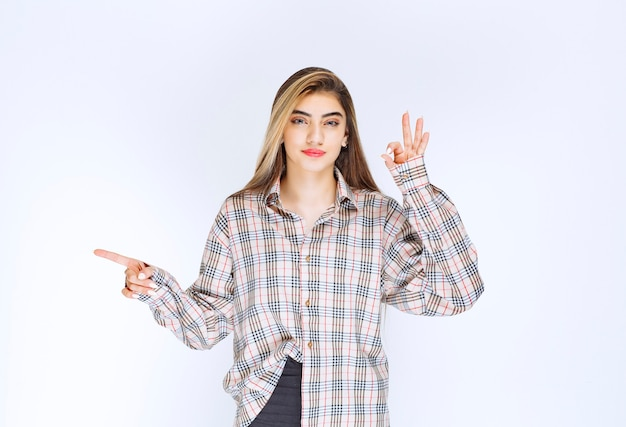 Ragazza in camicia a quadri che indica qualcuno intorno e mostra il segno della mano ok