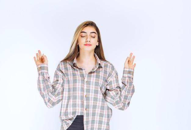 Ragazza in camicia a quadri che mostra il segno della mano ok