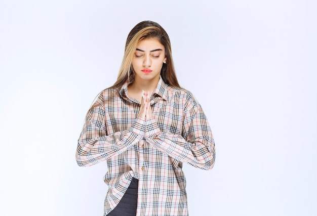 Girl in checked shirt uniting hands and praying