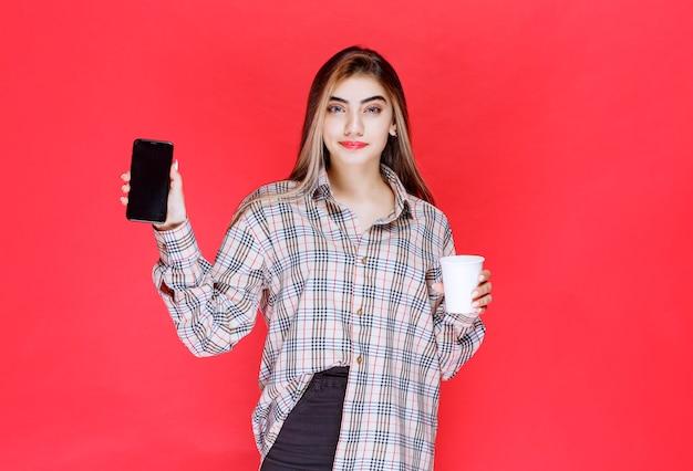 Ragazza con un maglione a quadri che tiene una tazza di bevanda e mostra il suo smartphone