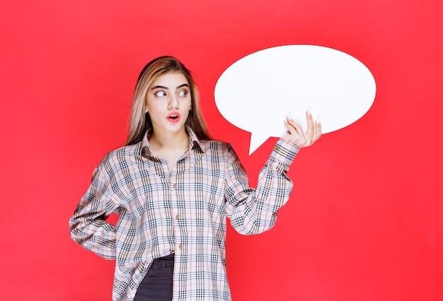 La ragazza con un maglione a quadri che tiene in mano un'ideaboard ovale sembra confusa ed eccitata