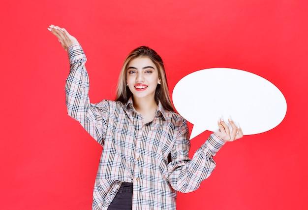 Ragazza con un maglione a quadri che tiene in mano un'ideaboard ovale e indica i partecipanti