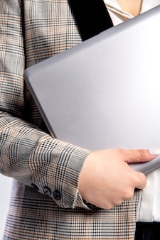 A girl in a checkered jacket holds a gray laptop in her hands