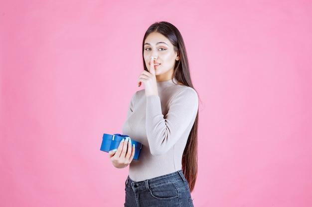 Девушка проверяет свою синюю подарочную коробку и выглядит взволнованной и удивленной