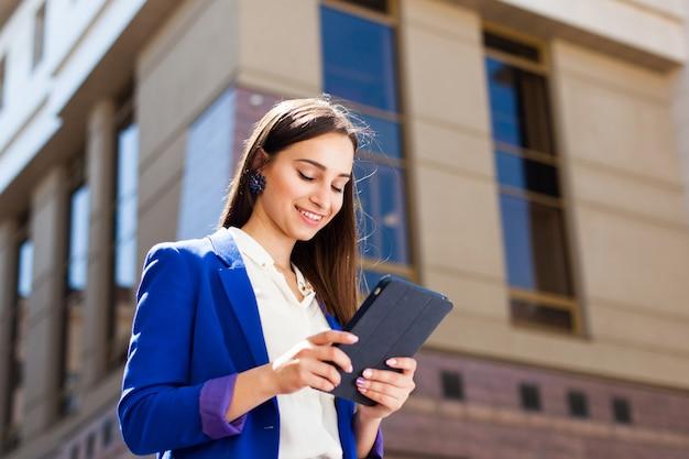 女の子は通りに立つ彼女のタブレットをチェックします 無料写真