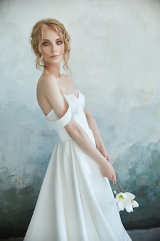 Girl in a chic long dress sitting on the floor. white wedding dress on