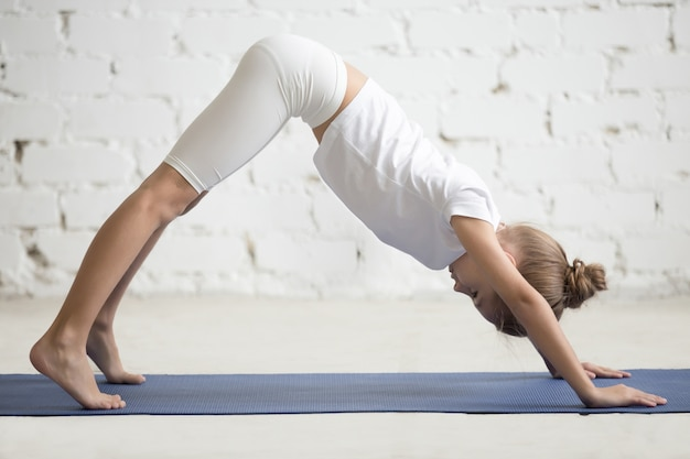 Girl child in adho mukha svanasana pose, white studio background