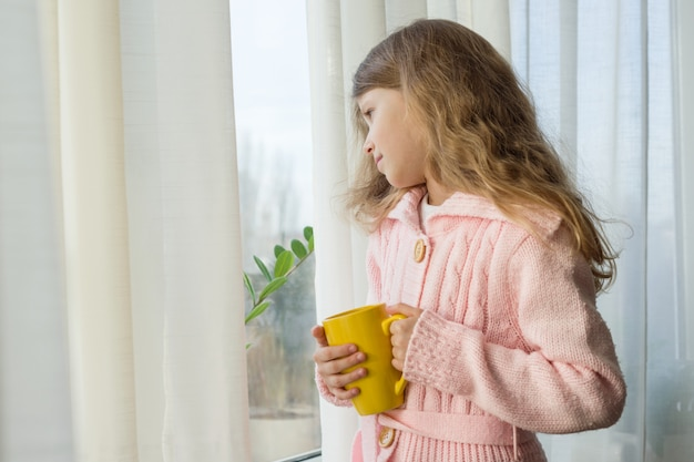 Girl child blonde holds a cup of tea and looks in the window