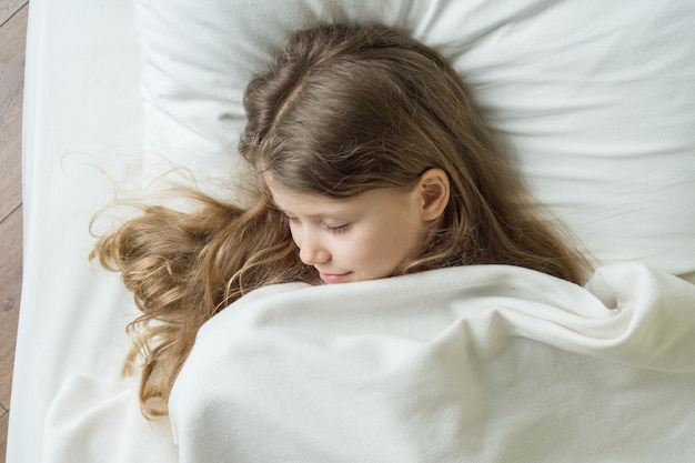 Girl child blonde with long wavy hair sleeping