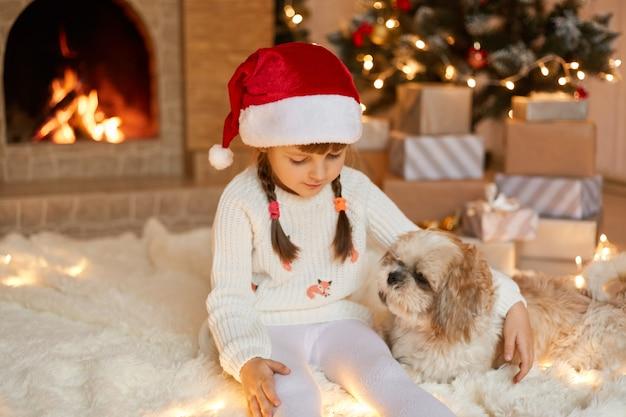 Girl child celebrates christmas with pekingese dog at home near christmas tree