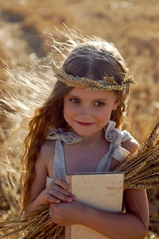 Girl child in a dress and a wreath on her head stands on a mown field of wheat at sunset in summer