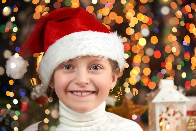 Девочки, одетые в новогоднюю шапку с рождественскими подарками на темном освещенном фоне