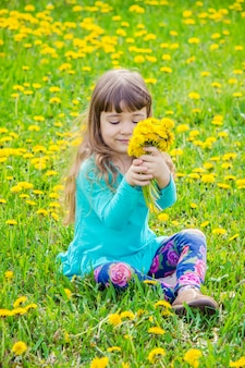 Girl, child, flowers in the spring plays.
