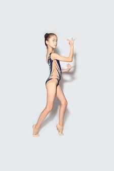 カメラを見て、白い背景で隔離の運動をしている女児体操選手。スポーツ、トレーニング、新体操、アクティブなライフスタイルのコンセプト。