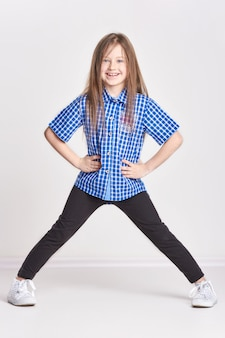Girl child having fun and posing in studio on a white background