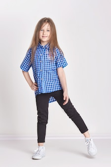 Girl child having fun and posing in studio on white