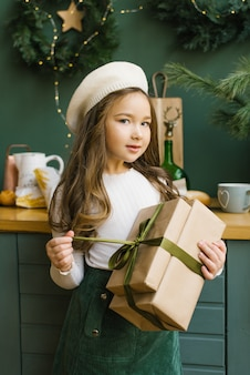 Girl child holding a christmas gift in a beige beret, beige sweater and turquoise skirt. unpacking a christmas gift