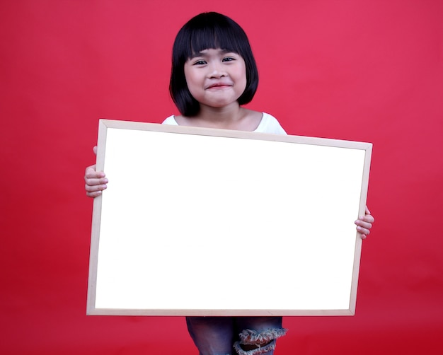 Girl child holding a message label.