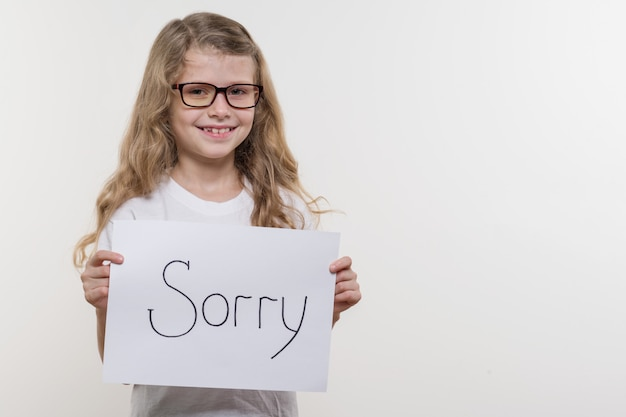 Girl child holding piece of paper with a word sorry