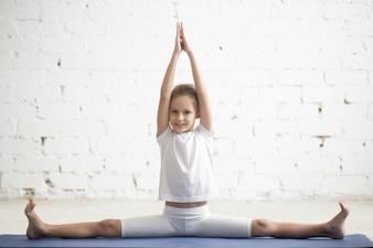 Girl child in Samakonasana pose, white studio background