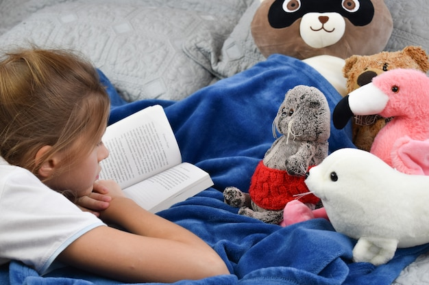 Girl child lies on the bed with a book and toys