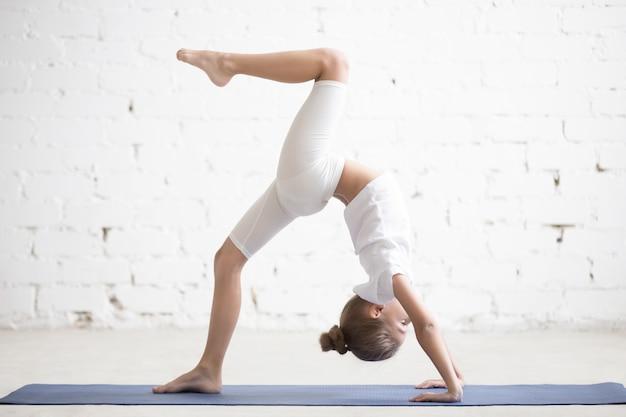 Girl child in one legged wheel pose, white studio background
