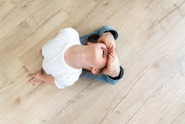 Girl child practicing yoga at home, stretching in raja bhudjangasana exercise, king cobra pose. top view