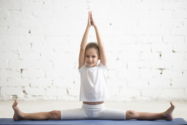 Girl child in samakonasana pose, white studio background